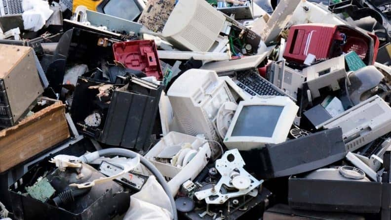 Image of discarded e-waste including broken computers, monitors, etc.