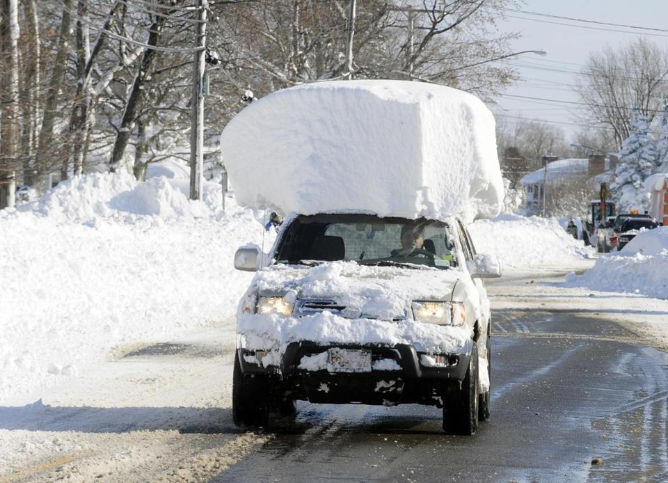 Car driving down residential street in winter environment with large amount of snow on roof