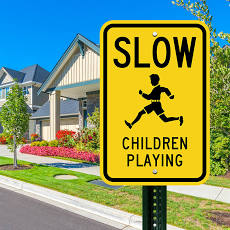 "Road sign with the words ""slow, children playing"" and including an icon image of a child runni"